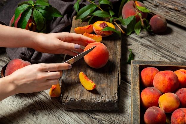Pesche frutti interi con foglie, pesche a metà, fette di pesca sul tavolo di legno. il processo di preparazione della marmellata di pesche, cottura del dessert alla pesca su tagliere rustico da mani femminili. umore scuro