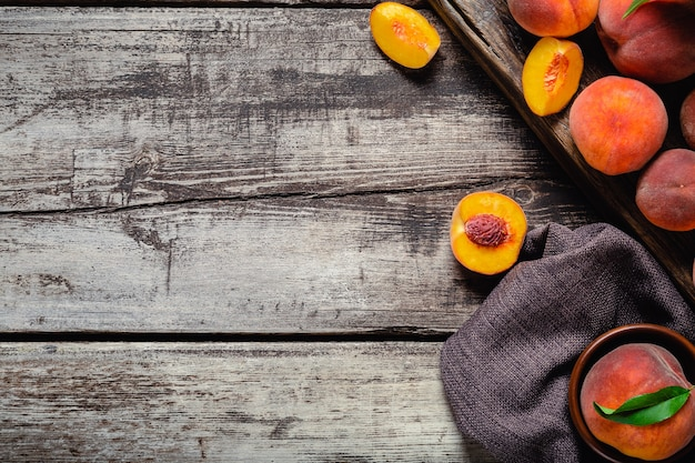 Pesche con foglie su tavola di legno scuro con pesca a metà. composizione con pesche succose mature. cornice di cibo. raccolto di frutta biologica fresca flat giaceva su un vecchio tavolo in legno rustico. spazio di copia vista dall'alto.