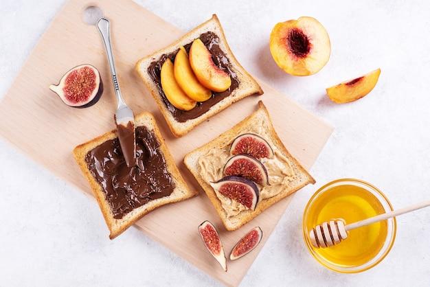 Burro di arachidi, cioccolato da spalmare con frutta su pane tostato su un tagliere su sfondo bianco, sana colazione dolce, primo piano.