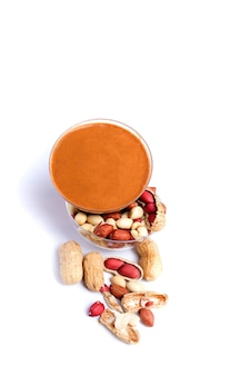 Burro di arachidi isolato e arachidi nella buccia sparse su fondo bianco. copia spazio.