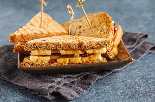 Panini al burro di arachidi con banana sul piatto scuro.