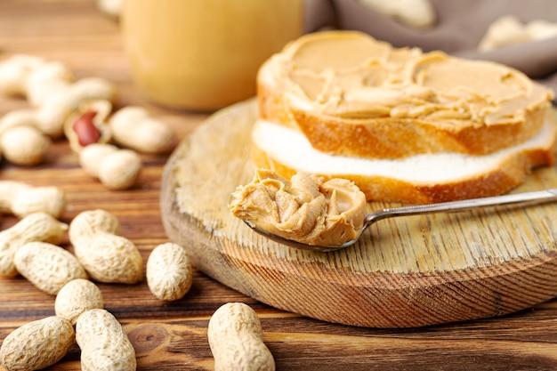 Burro di arachidi in cucchiaio vicino a pasta cremosa di arachidi in un barattolo di vetro aperto, fetta di pane al burro di arachidi, pane tostato. arachidi con la buccia sparse sul tavolo di legno marrone