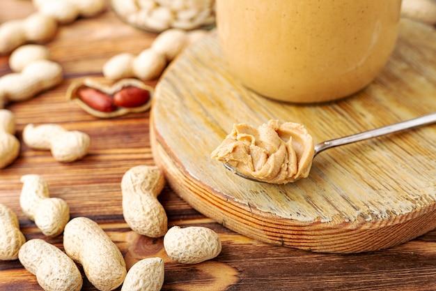 Burro di arachidi in cucchiaio vicino alla pasta di arachidi cremosa in barattolo di vetro aperto.