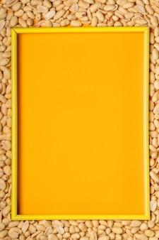 Cornice di arachidi con spazio libero. vista dall'alto. sfondo giallo brillante.