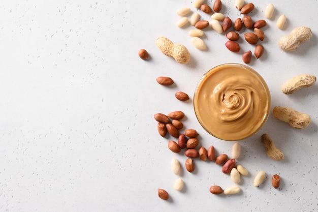 Pasta di arachidi e noci su sfondo bianco per una sana alimentazione concetto. vista dall'alto. spazio per il testo.