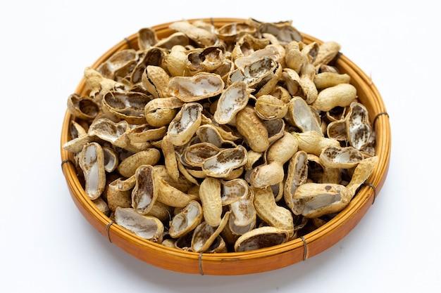 Gusci di arachidi in cesto di bambù su bianco