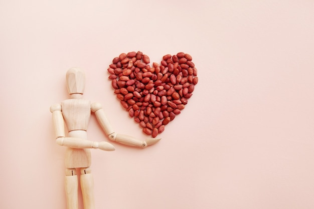 Le arachidi sono disposte a forma di cuore sulla mano di una bambola di legno arachidi crude