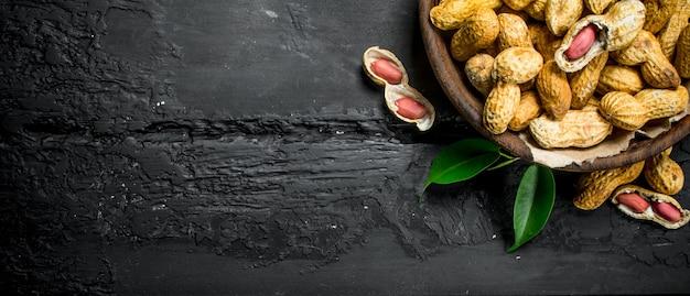 Arachidi in una ciotola con i fogli sulla tavola di legno nera.