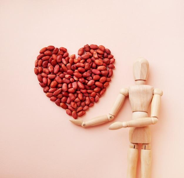 Arachidi a forma di cuore sulla mano di una bambola di legno arachidi crude su sfondo pastello