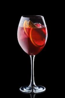 Sangria di pere e mele in un bicchiere di vino isolato sulla superficie nera