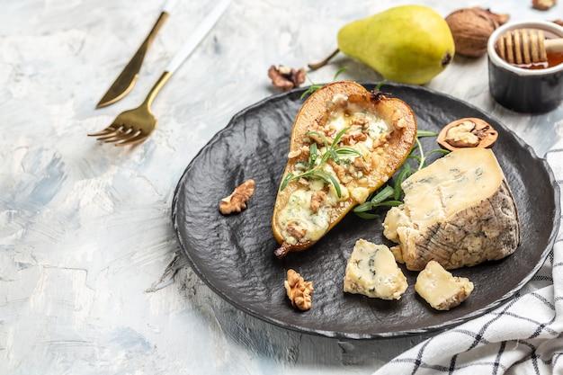 Pera e formaggio. pera al forno con formaggio blu, noci e miele, delizioso concetto di cibo equilibrato. sfondo di ricetta alimentare. avvicinamento.
