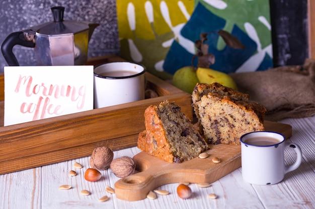 Torta di pere e tè con latte su un tavolo di legno