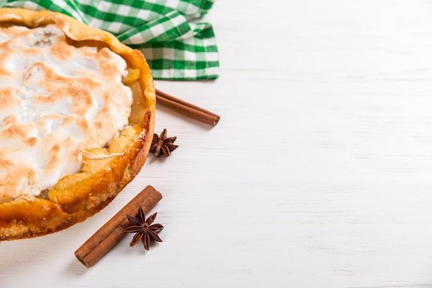 Torta di pere con panna, dolci fatti in casa sul tavolo con un tovagliolo verde.
