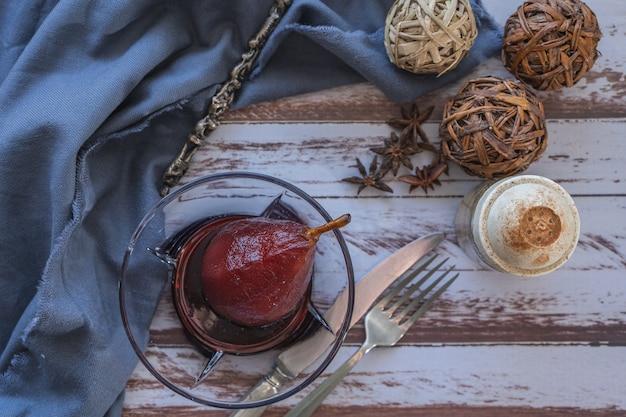 Pera con vino rosso servito in una ciotola di vetro in presentazione rustica su un tavolo di legno. vista aerea