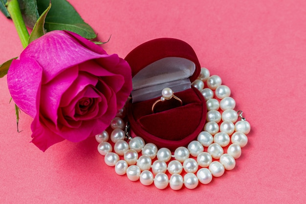 Anello di perle in scatola a forma di cuore, collana e una rosa. regalo di san valentino