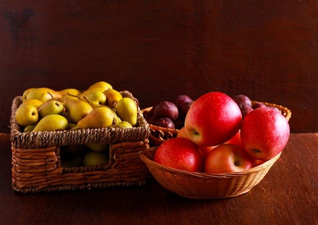 Pere, mele e prugne in cesti sul tavolo marrone