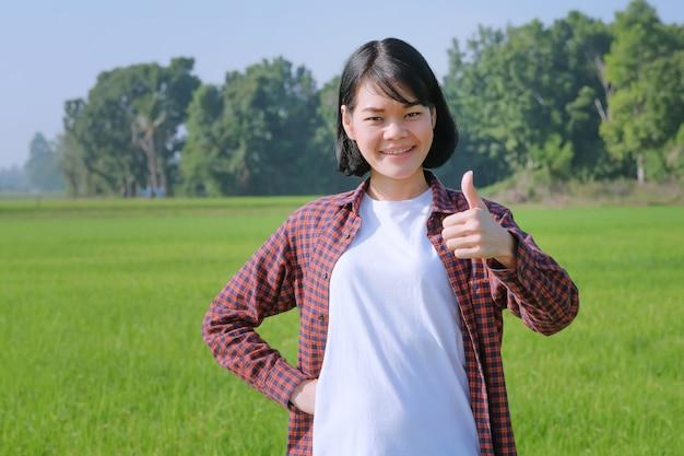 Una contadina con una camicia a righe posa per la gioia e il pollice in alto in un campo.