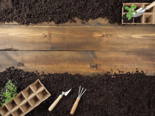 I vasi di torba e gli attrezzi da giardinaggio sono a terra. tavole di legno al centro. copia spazio. vista dall'alto.
