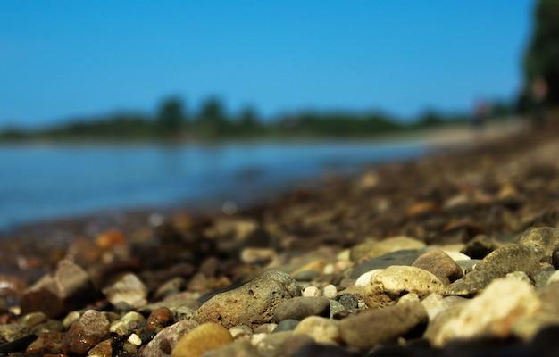 Pietre di ghiaia sulla riva si chiudono sullo sfondo sfocato della distanza. sfondo naturale.