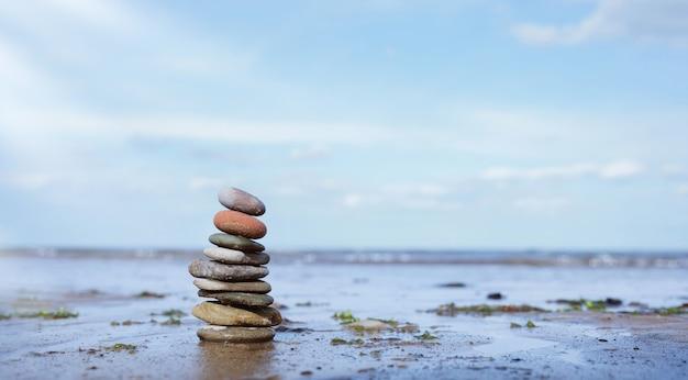 Torre di ciottoli in riva al mare con vista sul mare sfocata, pila di pietre di roccia zen sulla sabbia, piramide di pietre sulla spiaggia che simboleggia, stabilità, equilibrio di armonia con profondità di campo ridotta.