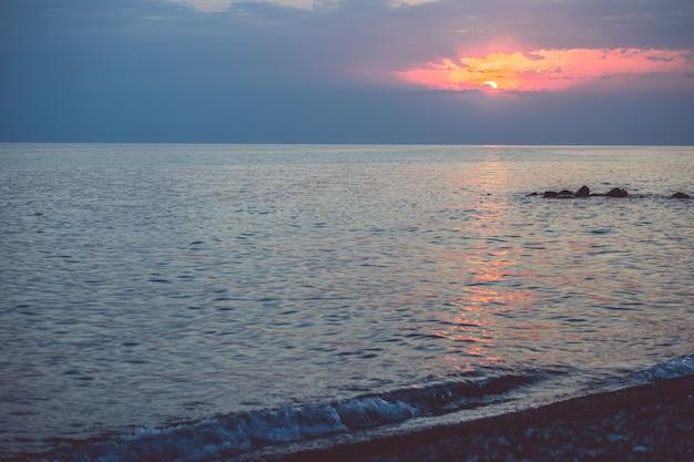 Ciottoli sulla spiaggia nella luce del tramonto. sfondo sfocato sotto i raggi del sole al tramonto.