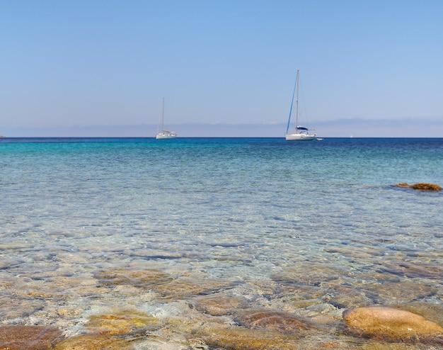 Ciottoli in acqua limpida con barca all'orizzonte - revellata - corsica