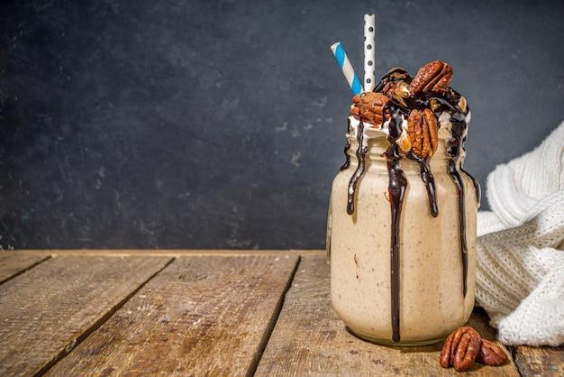 Frullato di torta di noci pecan. cocktail di frullato pazzo con il tradizionale sapore di noci pecan a torta autunnale, spazio di copia in legno di sfondo scuro