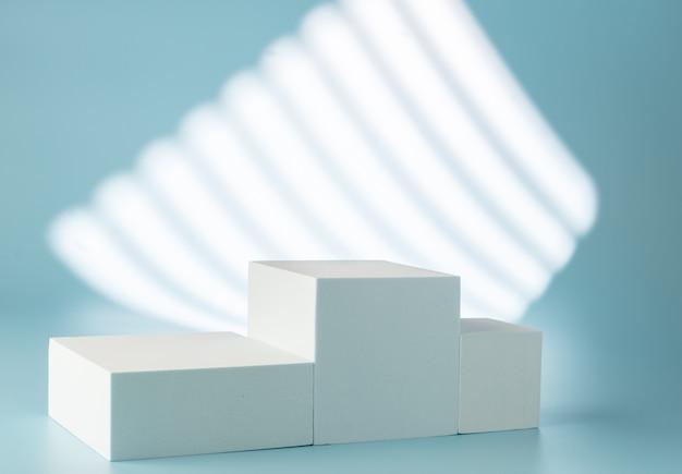 Piedistallo per la presentazione del prodotto su sfondo blu con ombre e luci