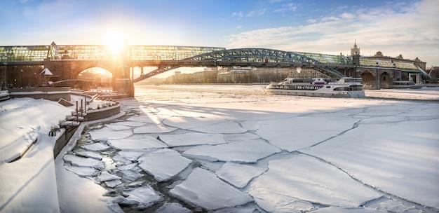 Il ponte pedonale andreevsky attraverso il fiume ghiacciato di mosca e una barca