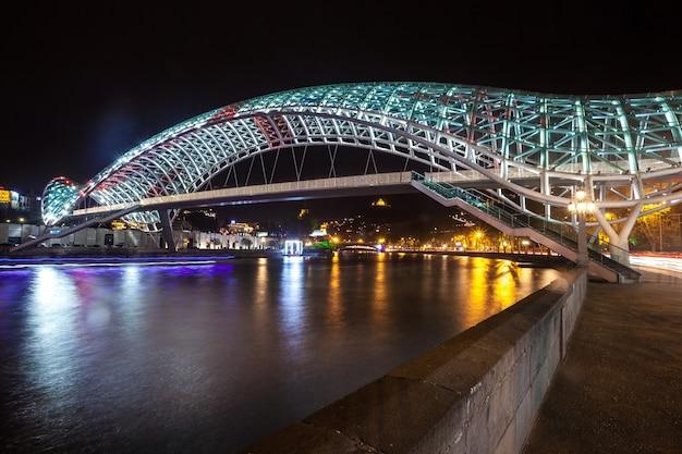 Ponte pedonale della pace sul fiume mtkvari (kura) a tbilisi di notte