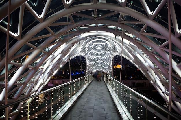 Ponte pedonale. la struttura in vetro d'acciaio illuminava numerose luci. concetto di architettura. ponte a tbilisi. il baldacchino in vetro sinuoso brilla di notte. ponte dal design moderno. destinazioni di viaggio.