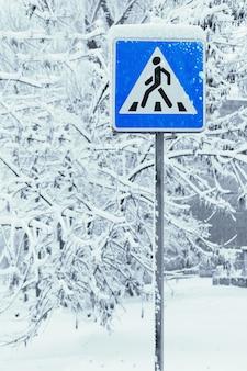 Segnale di attraversamento pedonale in inverno con alberi coperti di neve dopo la nevicata sulla superficie