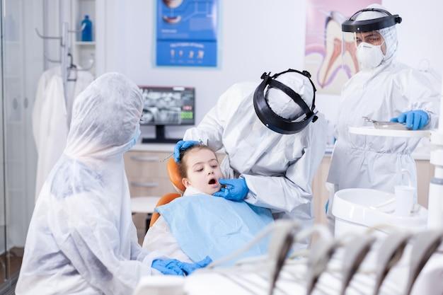 Stomatologo pediatrico che esegue la procedura di igiene orale su una bambina con pettorina che indossa tuta in dpi. dentista in tuta da coronavirus che utilizza uno specchio curvo durante l'esame dei denti del bambino.