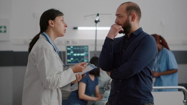 Dottoressa pediatrica che spiega i sintomi della malattia al padre mentre un'infermiera nera scrive una malattia medica...