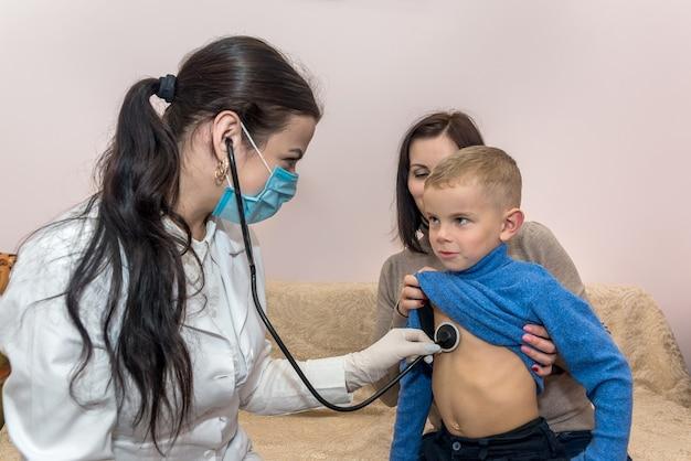Pediatra che controlla il battito cardiaco del piccolo paziente in visita