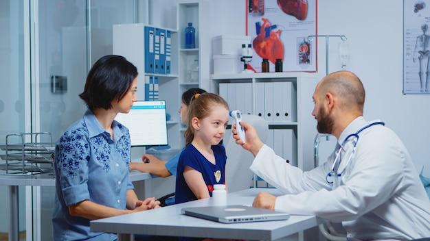 Pediatra che controlla la temperatura e infermiere che scrive sul computer. medico specialista in medicina che fornisce servizi di assistenza sanitaria consultazione esame diagnostico trattamento nel gabinetto ospedaliero