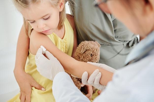 Sede di pulizia del pediatra con un tampone imbevuto di alcol