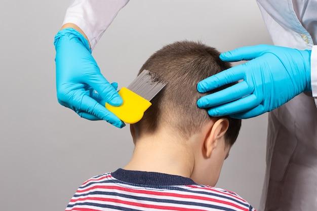 Il pediatra pettina i capelli del bambino con un pettine e cerca i pidocchi.
