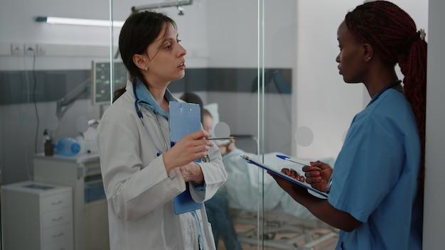 Medico pediatra che discute i sintomi della malattia con un'infermiera afroamericana che esamina la diagnosi scrivendo cure mediche mentre si lavora in corsia ospedaliera. bambino malato che riposa a letto durante la consultazione