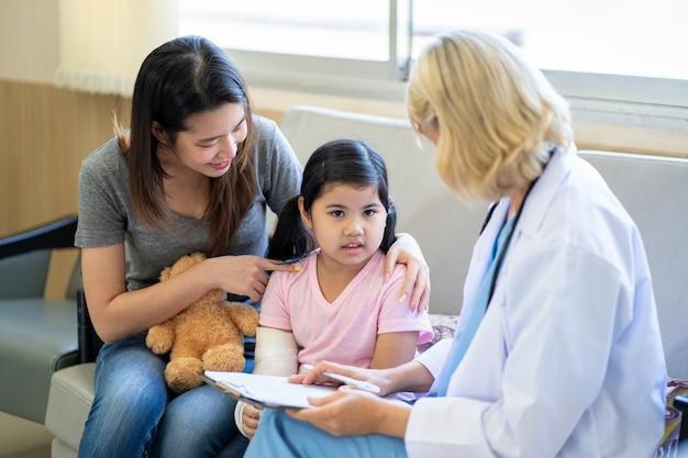 Medico pediatra che esamina una bambina asiatica con un braccio rotto che indossa un gesso all'ospedale