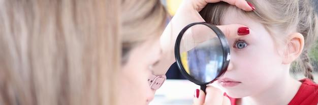 Medico pediatra che esamina l'occhio della bambina con la lente d'ingrandimento corpo estraneo dell'occhio in