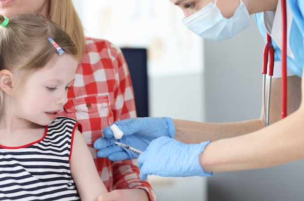 Il medico pediatra inocula la bambina nella spalla