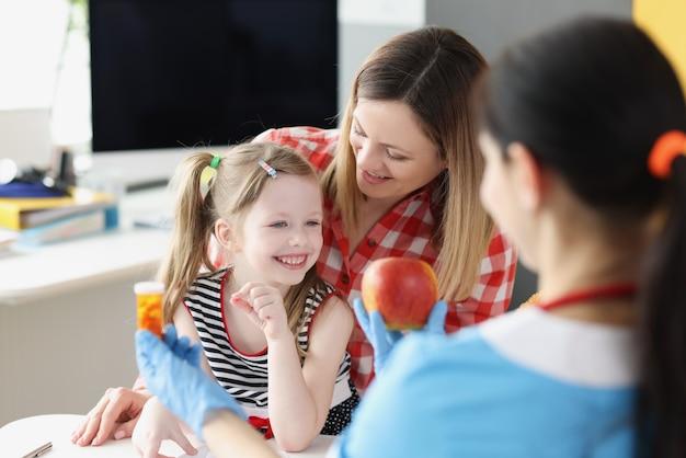 Medico pediatra che offre a madre e figlio mela o vasetto di medicina