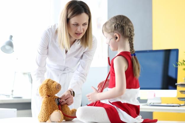 Il medico pediatra insieme alla bambina gioca la medicina con il giocattolo