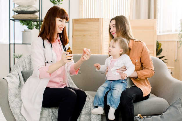 Pediatra che dà la dose di cucchiaio di sciroppo di liquido per medicina al paziente