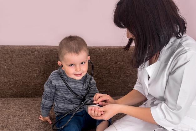 Pediatra che gioca con il ragazzino e lo stetoscopio