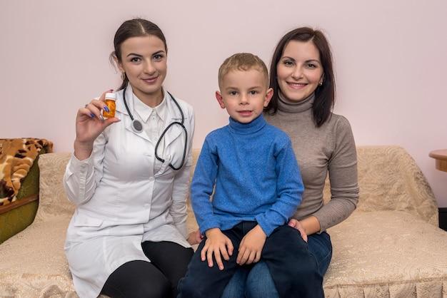 Pediatra con medicamento e ragazzo paziente con sua madre