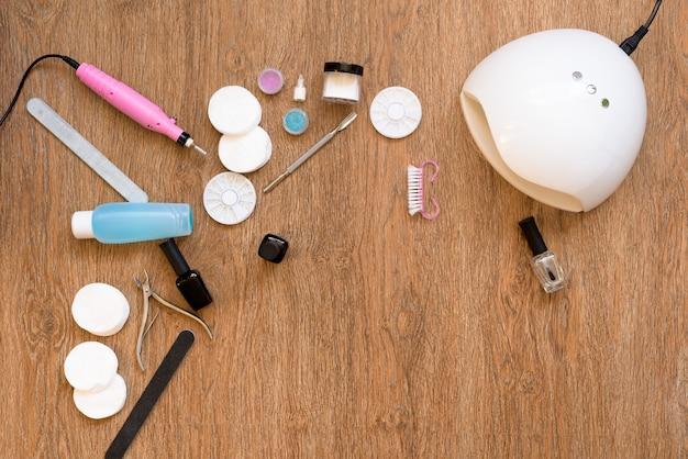 Pedicure a casa con smalto e lampade uv, lime per unghie e forbici. prendersi cura di sé e non uscire di casa. il processo di pittura per unghie e asciugatura in una lampada uv. vista dall'alto, layout piatto.