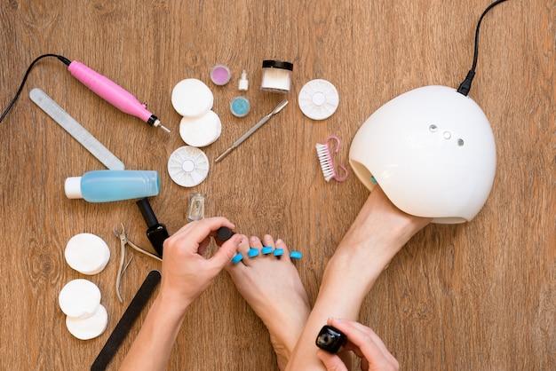 Pedicure a casa con smalto e lampade uv, lime per unghie e forbici. prendersi cura di sé e del proprio aspetto comodamente da casa propria. il processo di dipingere le unghie.