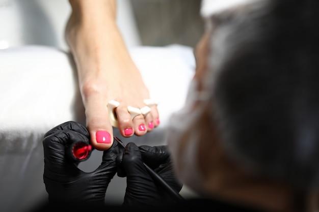 Il maestro di pedicure applica la vernice rosa alle unghie dei piedi cura igienica dei piedi in un salone di bellezza